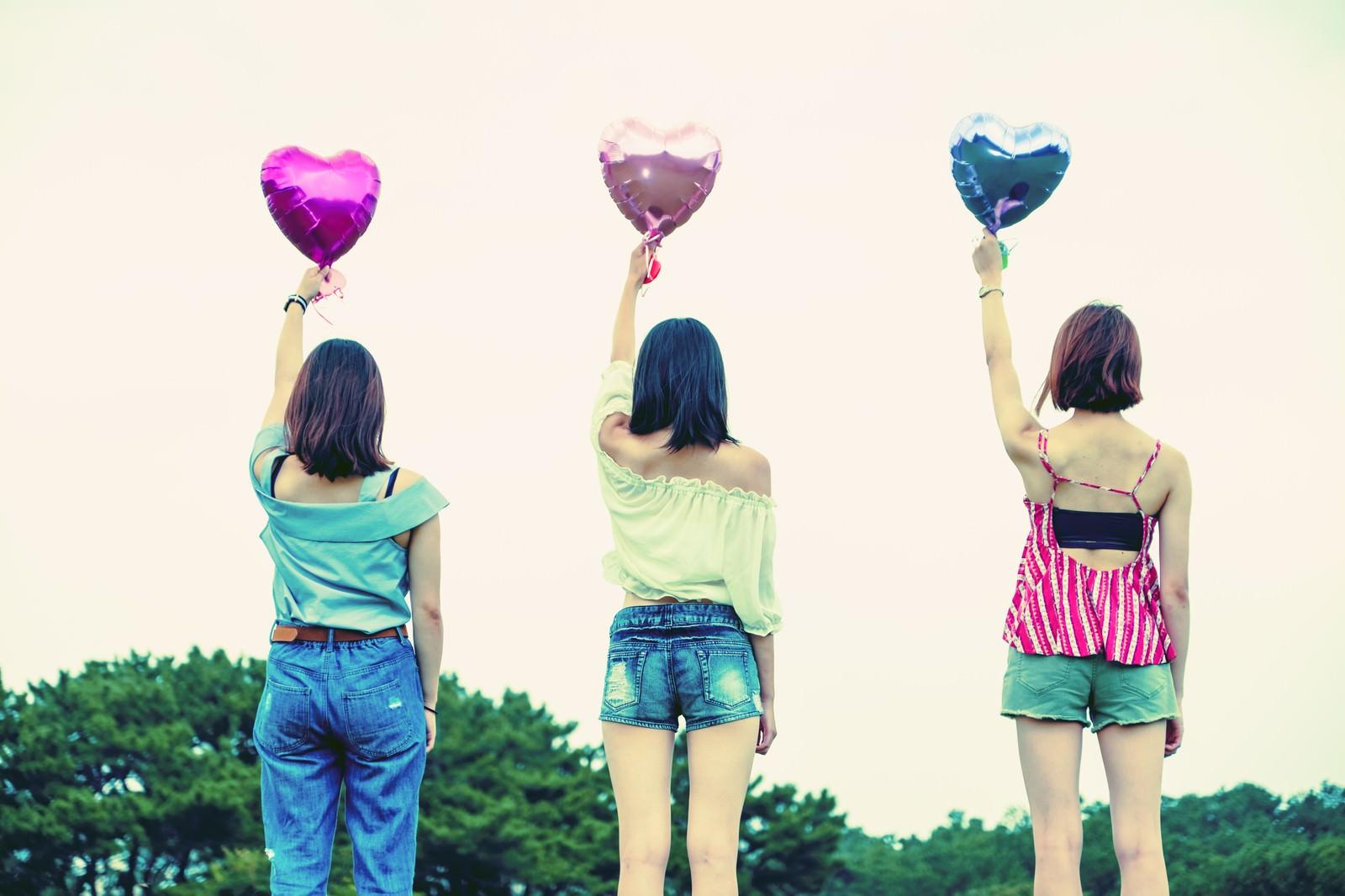 「ハートの風船を掲げる女子三人組」の写真