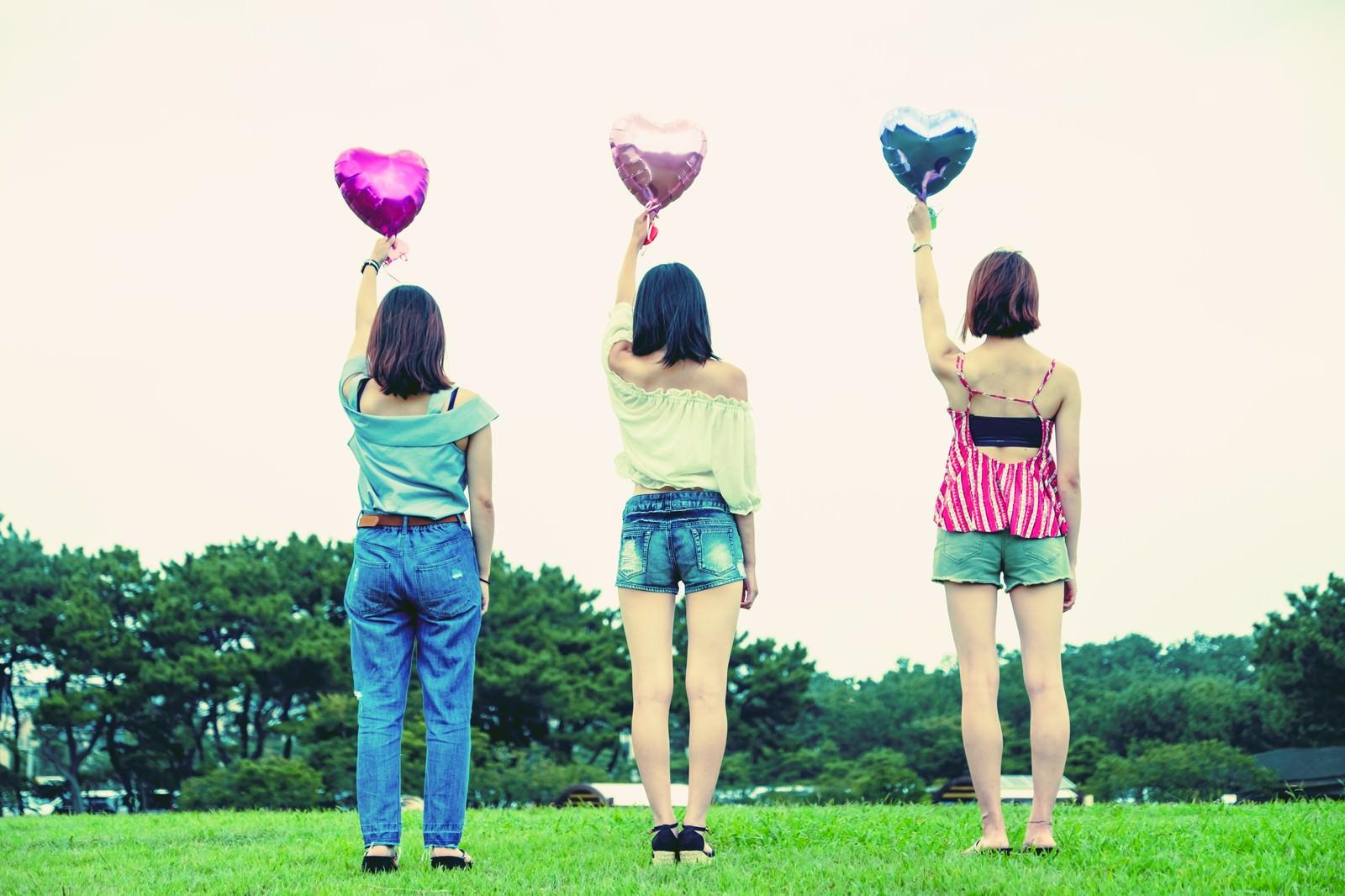 「ハートの風船を持った女子三人組の後ろ姿」の写真