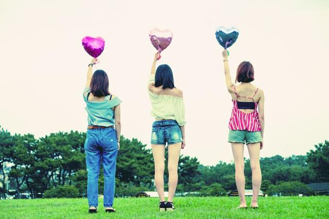 ハートの風船を持った女子三人組の後ろ姿の写真