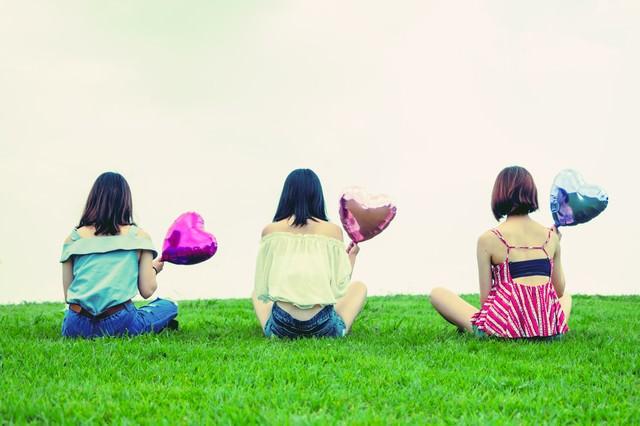 ハートの風船を持った女性の後姿(三人組)の写真