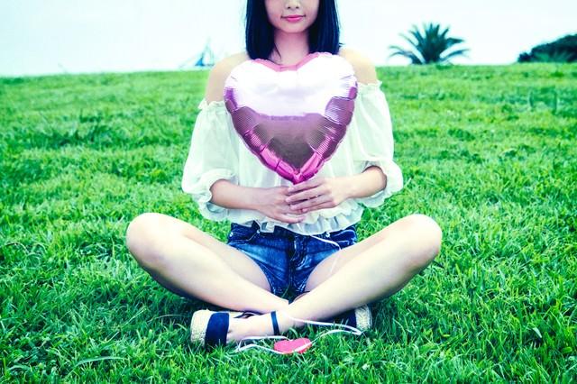 芝生に座る女子とハートの風船の写真
