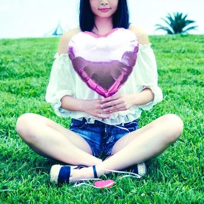 「芝生に座る女子とハートの風船」の写真素材