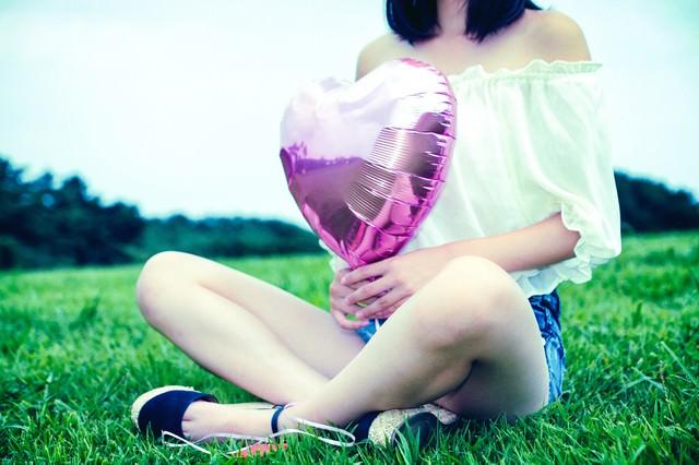 芝生の上でハートの風船を持って座る女子の写真