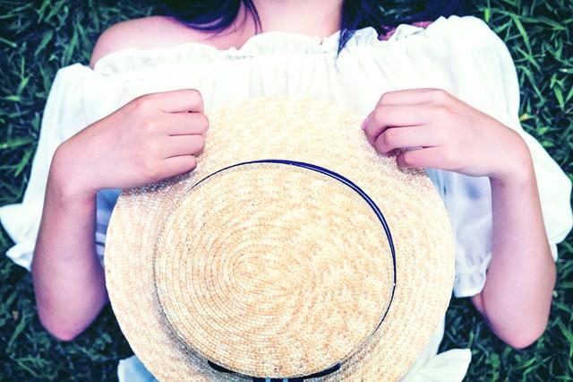 麦わら帽子を抱える女子の写真