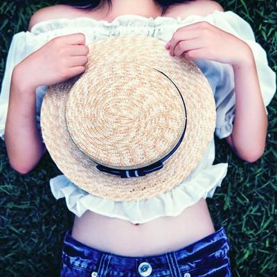 麦わら帽子を持って横になる女性の写真