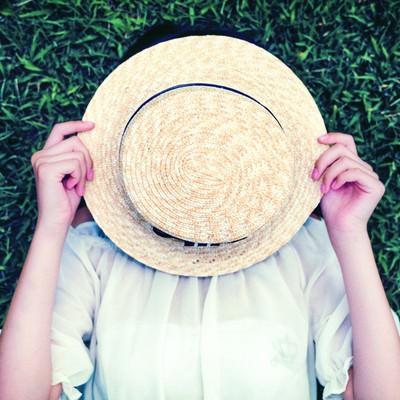 麦わら帽子で顔を隠す女の子の写真