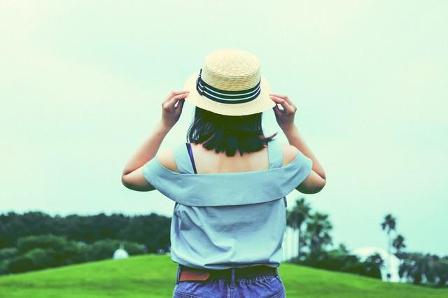 小さい麦わら帽子をかぶる女子の後ろ姿の写真