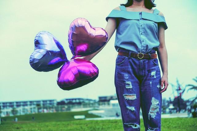 ハートの風船を持ったダメージジーンズ女子の写真