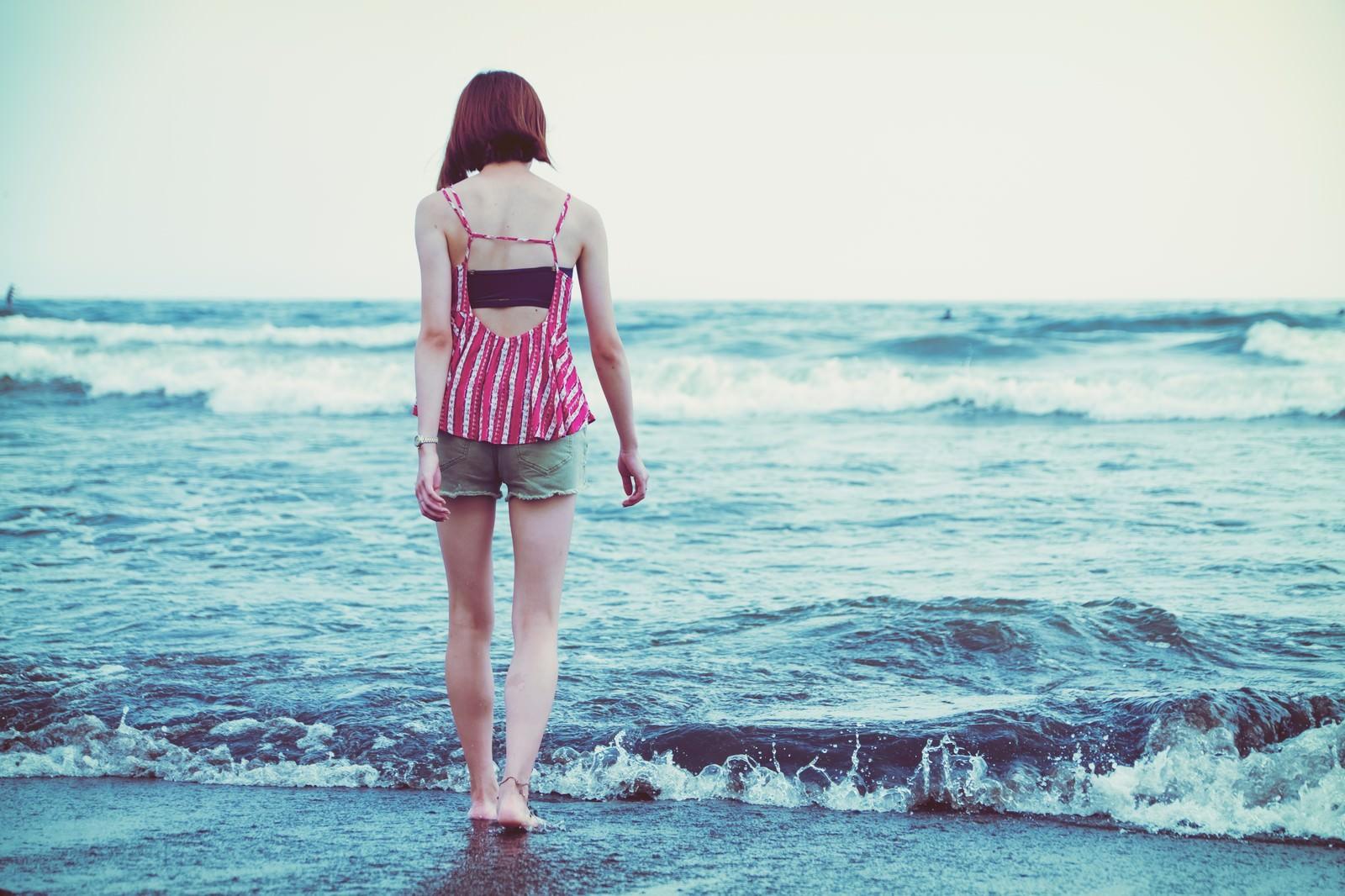 「波打ち際を裸足で歩く若い女性」の写真