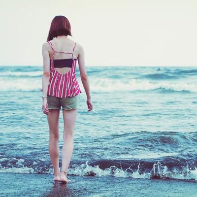波打ち際を裸足で歩く若い女性の写真