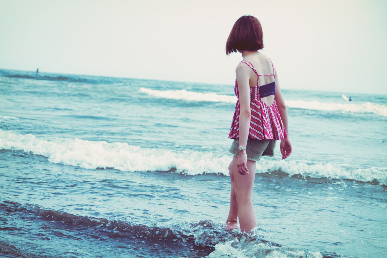 「海の波と浅瀬を歩く若い女性」の写真
