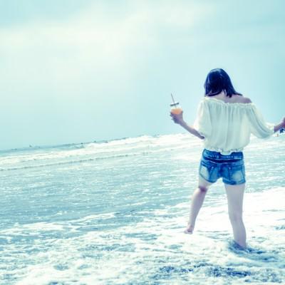 「浅瀬ではしゃぐ若い女性の後ろ姿」の写真素材