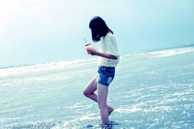 裸足で波打ち際に立つ女性の写真