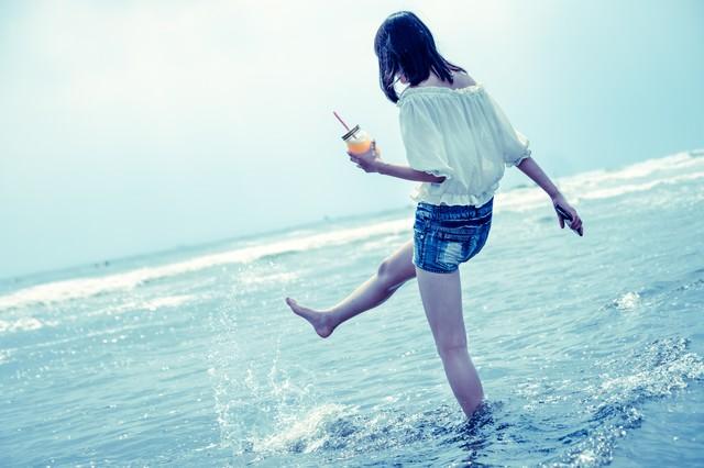 海面を蹴り上げる女性の写真