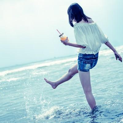 「海面を蹴り上げる女性」の写真素材