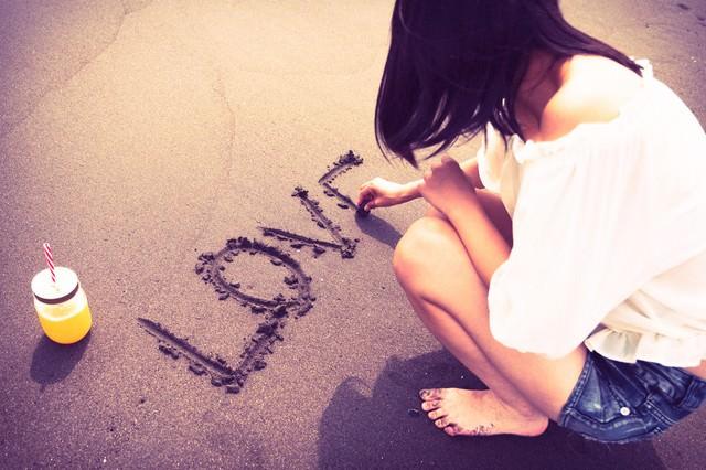砂の上にLOVEと文字を書く女性のうしろ姿の写真