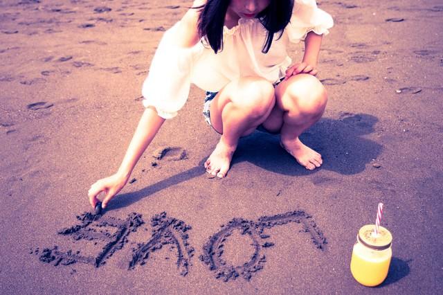 砂浜に「LOVE」を書く女の子の写真
