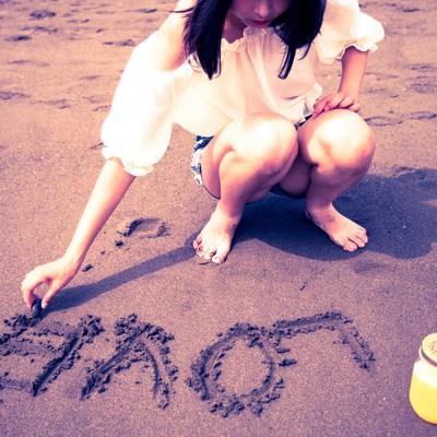 「砂浜に「LOVE」を書く女の子」の写真素材