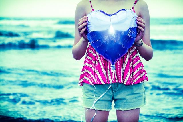海沿いでハートを抱えた女子の写真