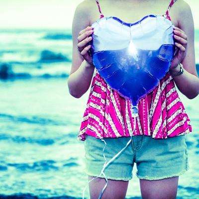 「海沿いでハートを抱えた女子」の写真素材