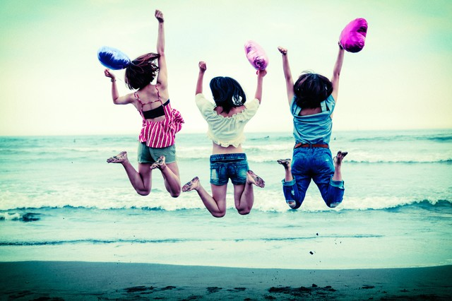 波打ち際でジャンプするハッピーな若い女性三人組の写真