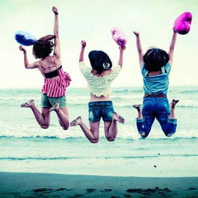 「波打ち際でジャンプするハッピーな若い女性三人組」の写真素材