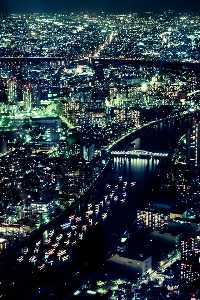 川を流れるカラフルな屋形船と都会の夜景の写真