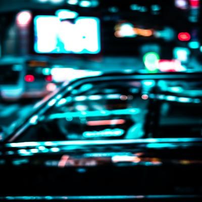 ネオンを反射するタクシーの写真