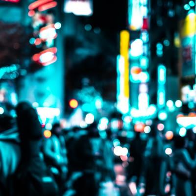 渋谷のネオンと交差点を行き交う通行人(夜間)の写真
