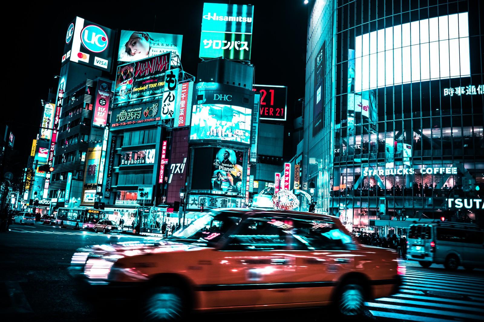 「渋谷のスクランブル交差点を走り抜ける車」の写真