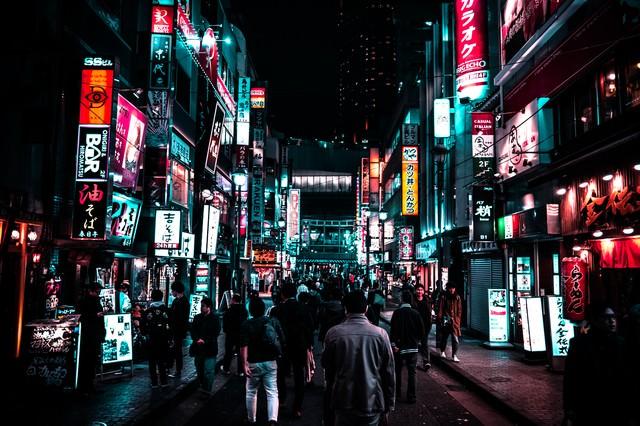 路地裏のネオン街を渋谷駅方向に歩く人の群れの写真