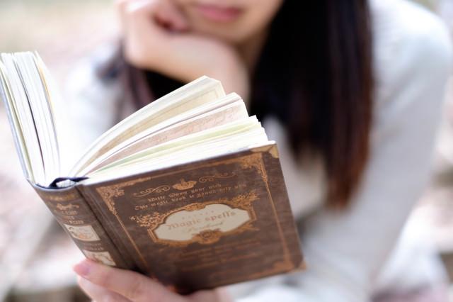 洋書を片手に時間を潰す女性の写真