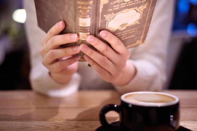 カフェで洋書を読む女性の手元の写真