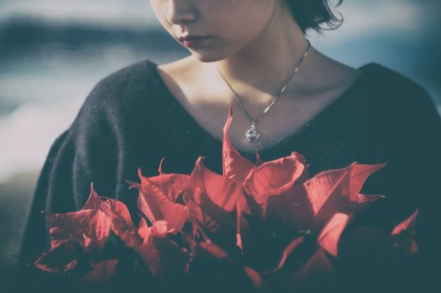 赤いポインセチアと虚ろな女性の写真