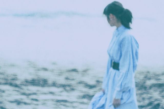 海辺を歩く彼女の写真