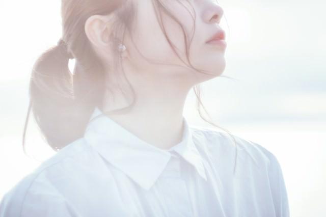 柔らかい逆光と寂しげな若い女性の横顔の写真