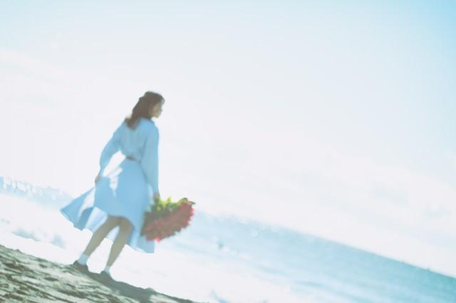 赤い花束を持った女性の後ろ姿の写真