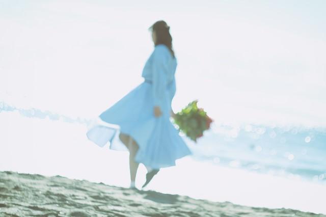 波打ち際を歩くスカートの女性の写真