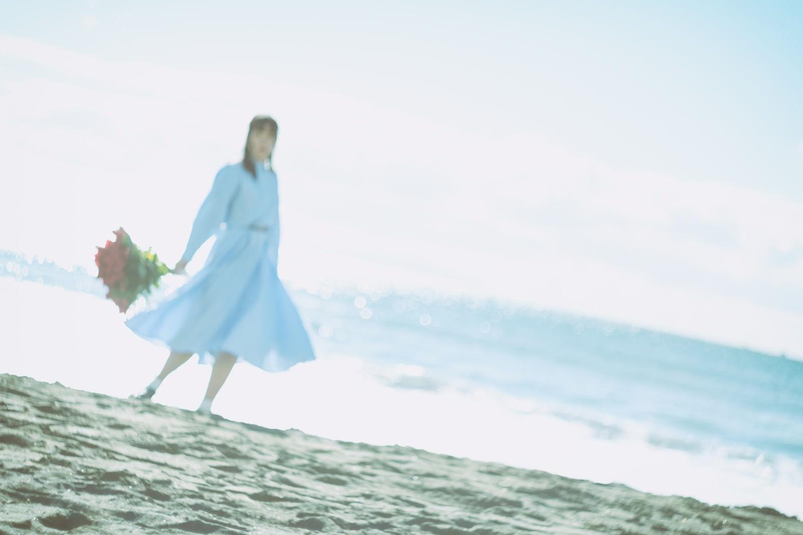 「爽やかな朝の海辺で花束を持つ女性」の写真