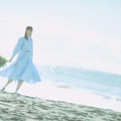 爽やかな朝の海辺で花束を持つ女性の写真