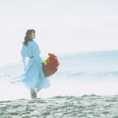 赤い花束を持ち砂浜を歩く女性の後ろ姿の写真