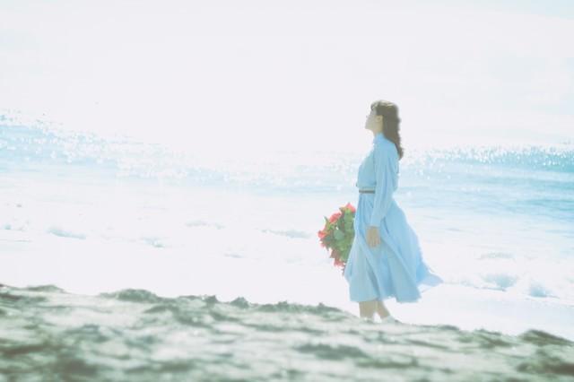 陽の光と海風を感じる女性の写真