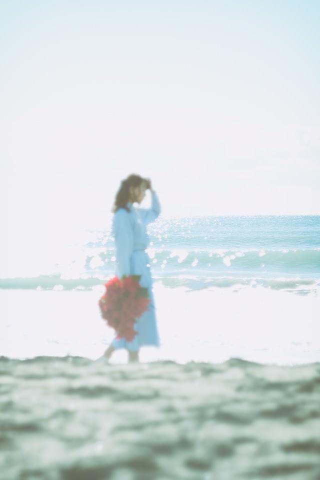 独り海岸線を歩く女性の写真