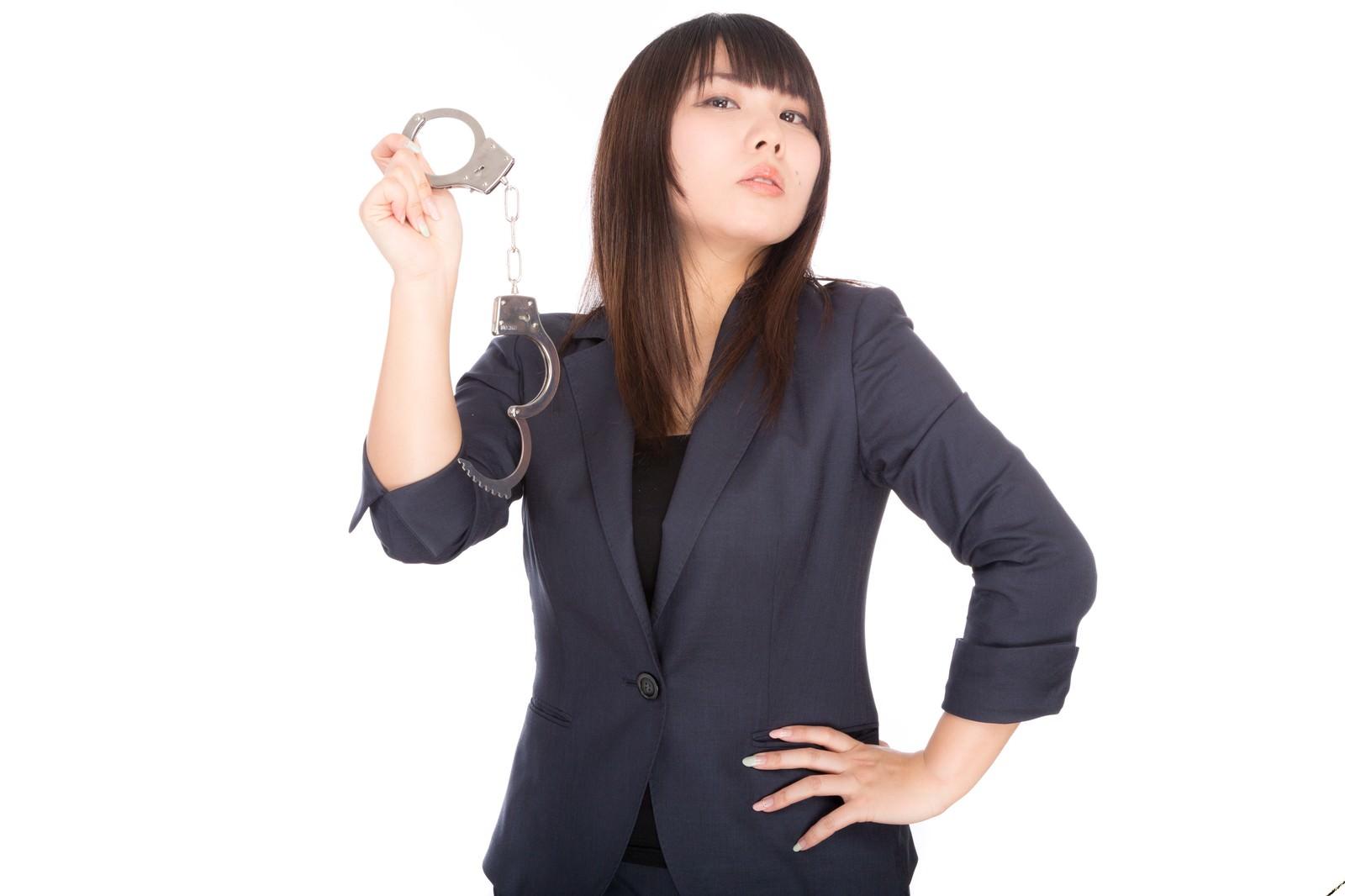 「手錠を掲げる高圧的な女性」の写真[モデル:Lala]