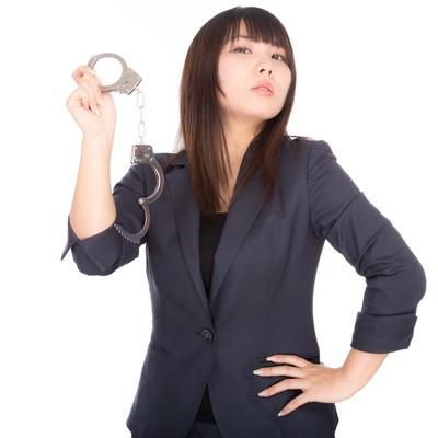 手錠を掲げる高圧的な女性の写真