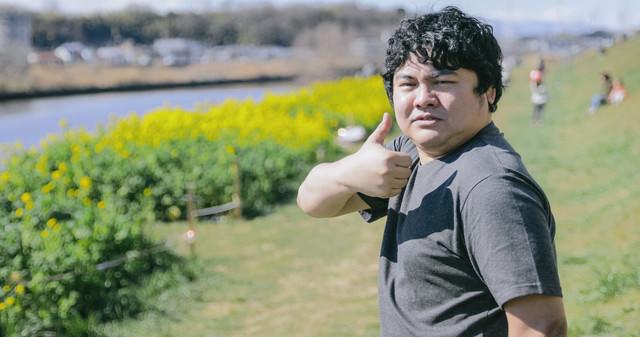 菜の花畑でサムズアップの写真