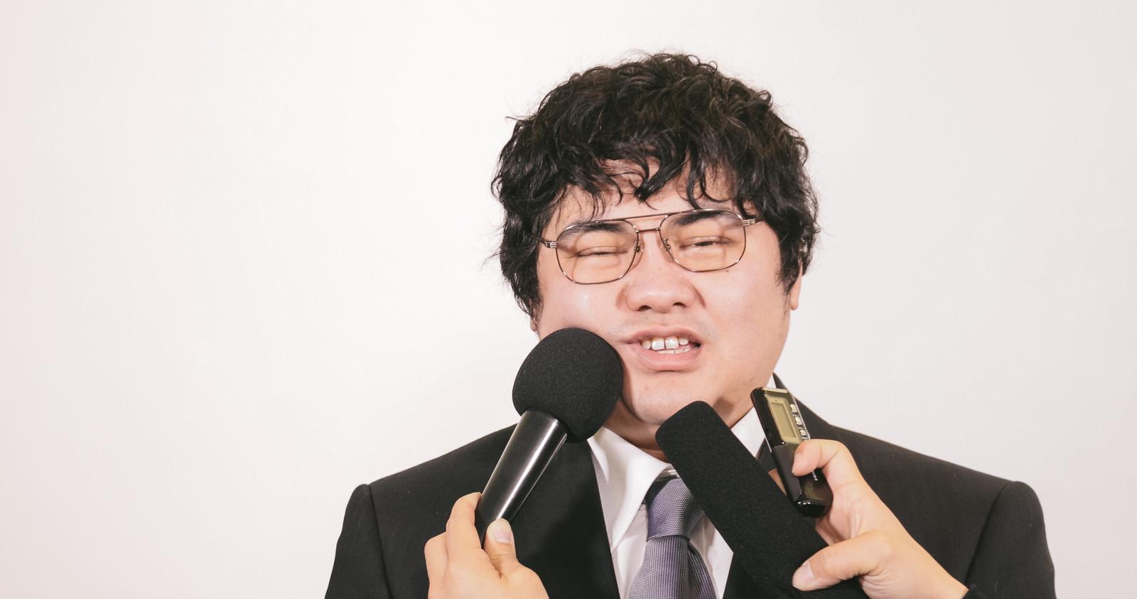 「過剰なインタビューで困惑する責任者」の写真[モデル:段田隼人]