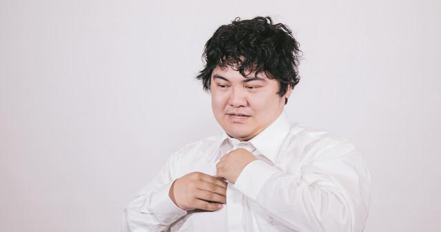 仕事が終わりワイシャツを脱ぐビジネスマンの写真