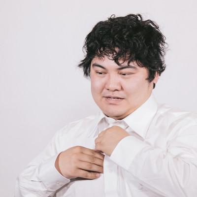 「仕事が終わりワイシャツを脱ぐビジネスマン」の写真素材