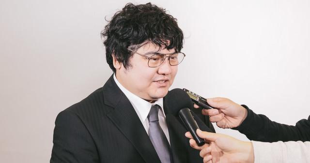 売却問題で報道陣に取材を受ける男性の写真
